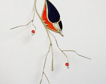 Stained glass red breasted nuthatch bird on a 3-dimentional tinned wire branch with red berries.