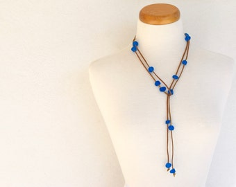 Resin bead lariat necklace azure blue assorted shaped resin beads spaced along gold suede cord can be worn as a belt too