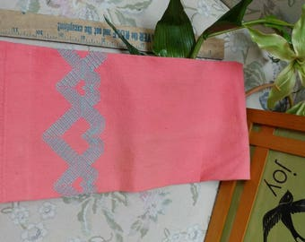Bright pink coral tea towel with blue decorative stitching. Some discoloration- vintage.