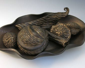 Collection of carved porcelain pods in tray, bronze glaze, metallic