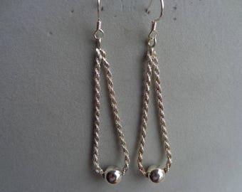 Dangling silver chain/ bead earrings.