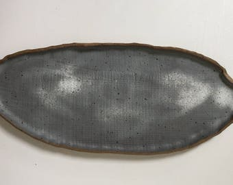 Organic, oblong serving tray, with matte grey glaze and white accents with dark grey speckles and unglazed brown rim.