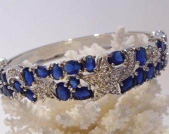 Rhinestone Star Hinged Bangle Bracelet of Silver Tone Metal and Sapphire Blue Stones Great for Prom