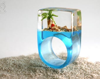 Sommerfrische – Sommerlicher Strand-Figuren-Ring mit zwei Badenden, Palme und Sand auf hellblauen Ring in Gießharz für Urlaubsstimmung