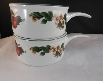 A pair of soup mugs, white with apple blossoms and apples around them and handles.