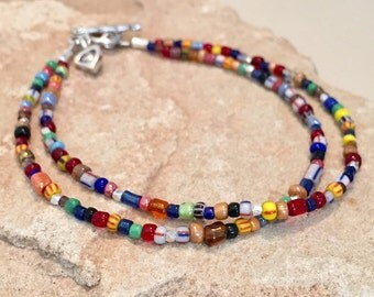Multicolored double strand bracelet made with Ghana seed beads, Hill Tribe silver faceted and tube beads and silver toggle clasp and charm