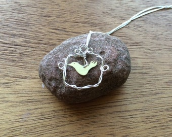 Silver necklace with a bird in a frame