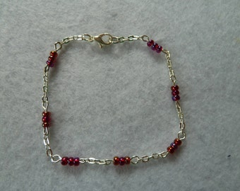 Silver bracelet with red shimmering beads