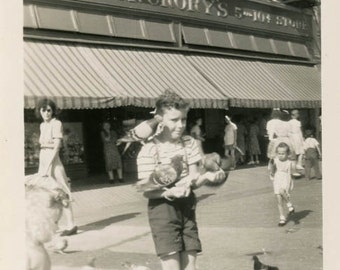 Vintage photo snapshot 1955 Boy Feeding the Birds out in the Street.