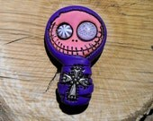 Adorable baby mummy bandaged in deep purple. Creepy and cute skull with a cross on his chest. Brooch or magnet