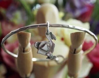A cute little fine silver dodo charm on a hand beaten sterling silver bangle..