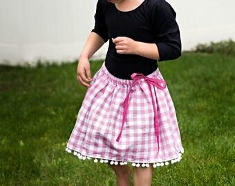 Girls twirly pink gingham skirt with pompom trim, ball fringe, tie waist, sizes 12 m to 12 years drawstring