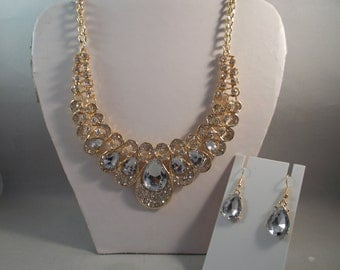 Bib Necklace with Gold Tone, Clear Teardrop Crystal Beads and Clear Rhinestone Pendants on a gold tone chain with Matching Earrings