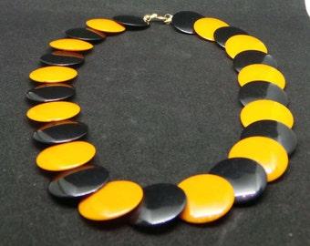 Vintage plastic necklace in black and butterscotch orange.