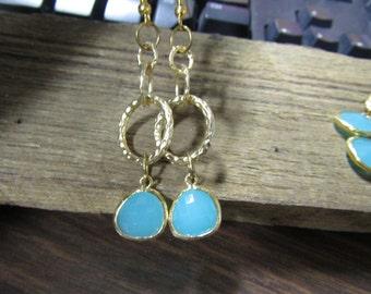Mint green dangle earrings in a gold setting