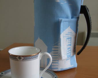 An attractive cotton padded cafetiere cover in a seaside design of white beach huts on a blue background