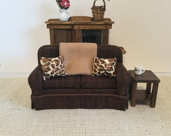 Traditional Couch in Brown with two pillows and blanket
