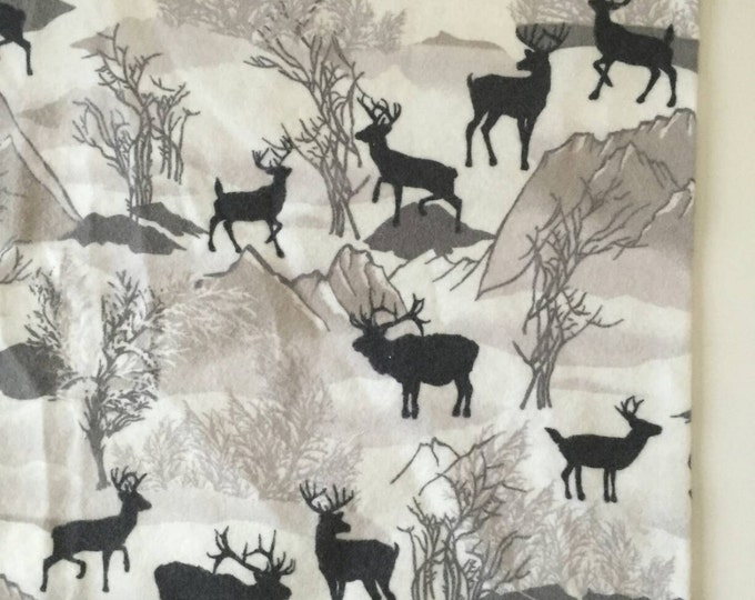 Grey deer and mountains receiving blanket