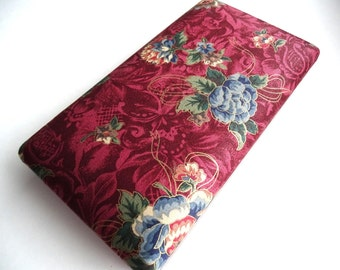 Vintage jewelry case with a burgundy paisley and blue cabbage rose fabric covering and gold tone metal trim.