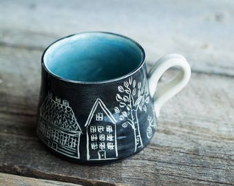 Turquoise black pottery mug with houses and trees