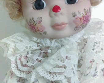 Porcelain Doll. Dynasty Doll Collection.  Clown wearing a Floral  Romper Clown Costume  with Lace and Ribbons Including a Hat.