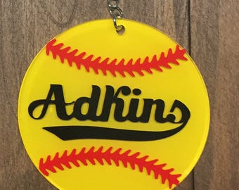 Personalized softball acrylic keychain with yellow vinyl, red stitches, and black name.