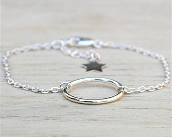 massive silver oval ring on chain bracelet
