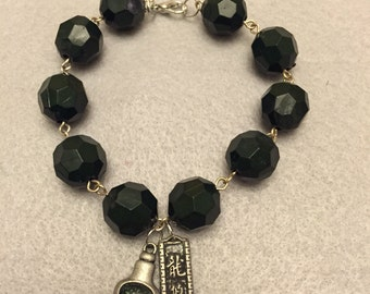 Dark green beaded chain bracelet with Asian inspired charms.