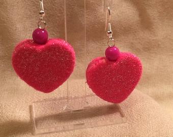 Fluorescent pink heart earrings glistening