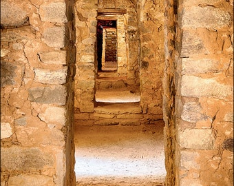 Ancestral Puebloan ancient room structure with stone walls and multiple doors at Aztec ruins in New Mexico.  Architectural door photography.