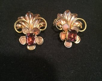 Clip on earrings with a plum rhinestone in a bronze floral setting