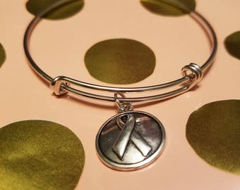 Silver bangle with breast cancer awareness charm
