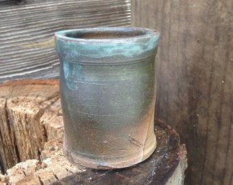 Experimental mugs and cups: dark green mistake cup by Joel Patton