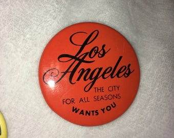 "1 Vintage mid 80s Medium-dark Orange Pin ""Los Angeles The City For All Seasons Wants You"" with Black Font"