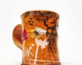 Floral mug with orange glaze and white decals