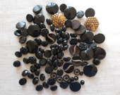Vintage black glass assorted size and design sew hole and shank glass buttons. Lot of 94 buttons.