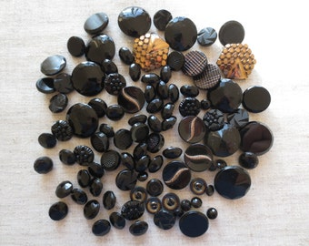 Vintage black assorted size and design sew hole and shank glass buttons. Lot of 94 buttons.