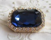 Vintage Gold Tone Brooch with Large Rectangular Navy Blue Faceted Rhinestone Surrounded by Small Clear Rhinestones