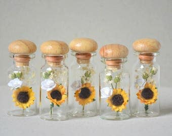 5   paper flowers  and dried flowers  in glass bottles