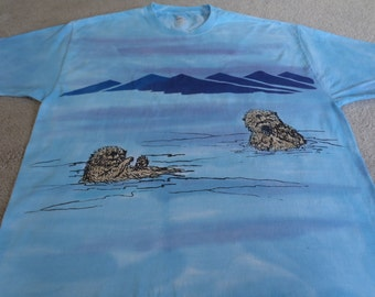 Adorable sea otters with a sea urchin, mountain range in the background, man's Hanes 2XL t-shirt, screen printed and dyed, blues and violet
