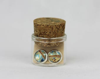 Small silver studs covered in Japanese paper packaged in glass bottle