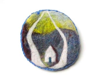 Felted pin, wearable art piece with a cottage and woodland landscape.