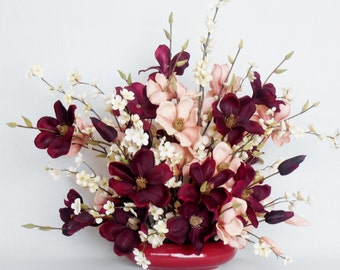 Plum & Peach Magnolia Blossoms along with Branches of Tiny Cream Blossoms in a maroon vase.