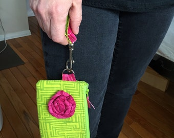 Wristlet zippered clutch is convertible from small to medium size