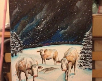 Cows in a snowy field at night