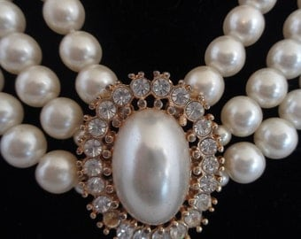Vintage Faux Pearl Necklace with a Center Faux Pearl Surrounded by Rhinestones. There are Three Strands of Pearls.