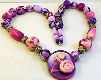 Beaded necklace. Hand made set of beads with large purple, pink and cream feature bead.