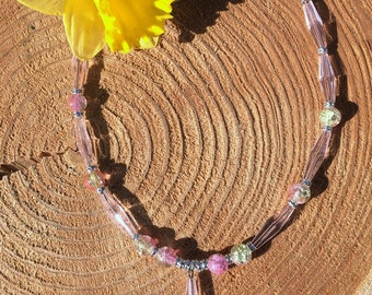 Summer necklace with elongated pink beads and a metallic heart in the middle.