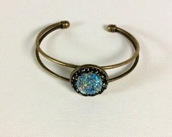 Light blue  druzy surrounded by small black rhinestones on a bronze cuff bracelet