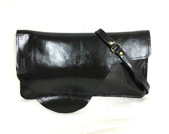 Beautiful handcrafted, multi-purpose black leather bag. Black leather clutch with a detachable carrying strap. For everyday use. For her.